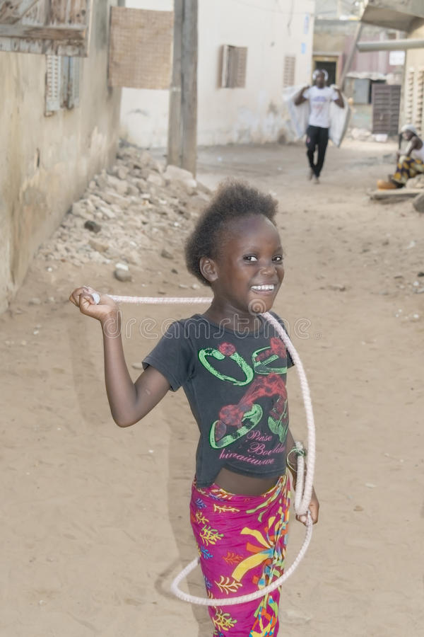 Editorial caption: THIAROYE, SENEGAL, AFRICA – JULY 28, 2014 – Unidentified girl playing with a jump rope in the street royalty free stock photography