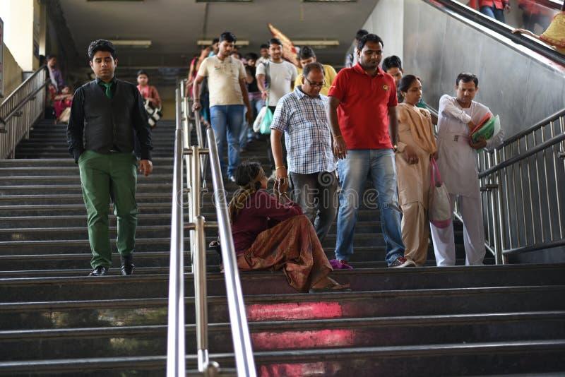 Editorial: Gurgaon, Deli, Índia: 7 de junho de 2015: Uma mulher pobre idosa não identificada que implora dos povos na estação de  foto de stock royalty free