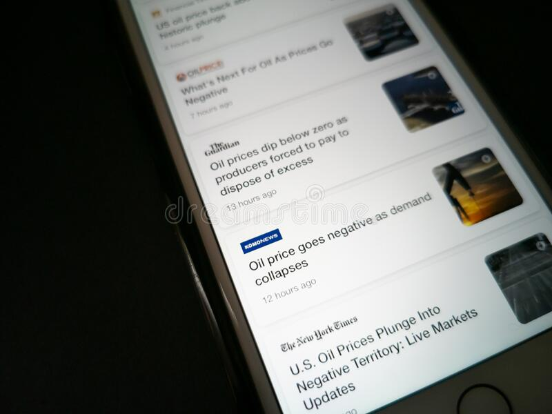 EDITORIAL ILUSTRATIVO - CIRCA ABRIL 2020 : Screengrab de um iPhone da Apple sobre notícias sobre queda do preço do petróleo bruto fotografia de stock