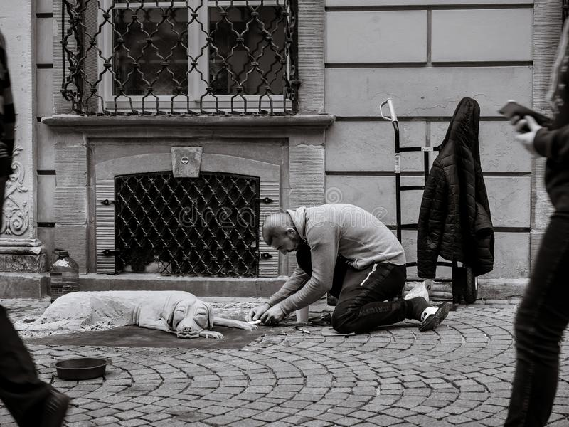 Editorial: 22nd September 2019: Strasbourg, France. A man sits on the ground in the street and sculpts a dog from the sand royalty free stock photography