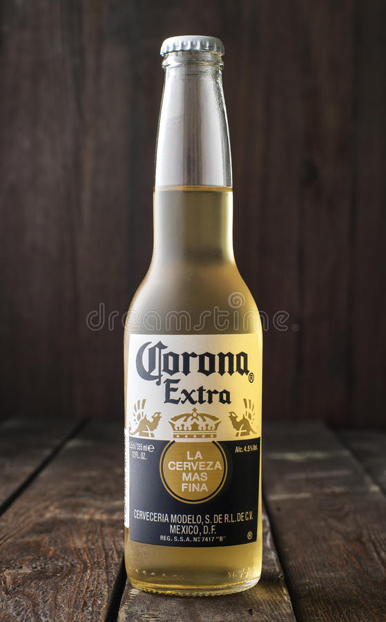 Editorial photo of bottle of Corona Extra Beer on dark wooden background. MINSK, BELARUS - MARCH 27, 2017: Editorial photo of bottle of Corona Extra Beer on dark stock image