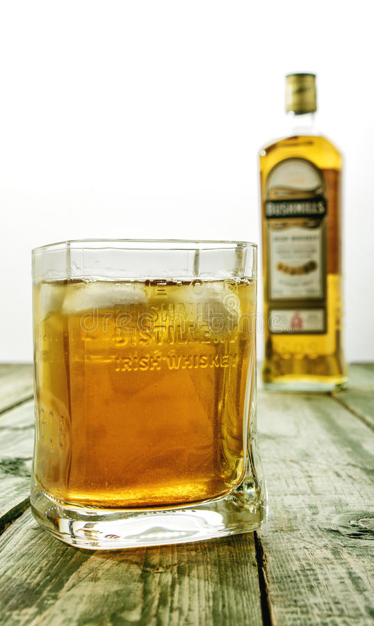 Editorial photo of Bushmills whiskey glass with logo and blurred bottle in background. MINSK, BELARUS - MARCH 10, 2017: Bushmills whiskey glass with logo and stock photography