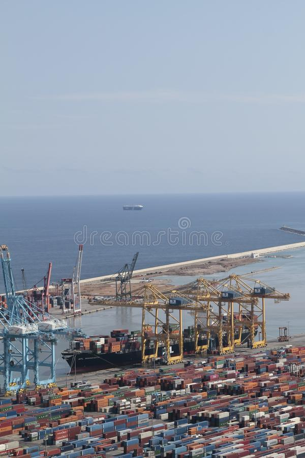 Barcelona industrial harbor with cranes containers and cargo ship being loaded stock image