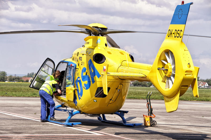 Editorial - technicians by the yellow medical helicopter royalty free stock images