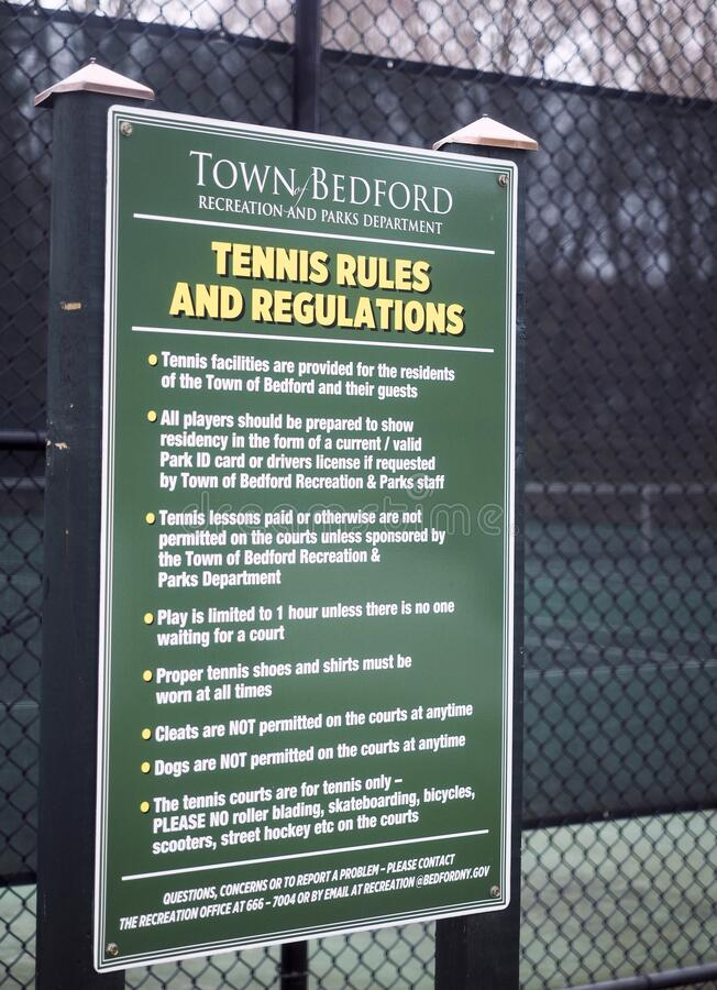 Editorial tennis rules regulation sign public town courts Bedford, New York royalty free stock image