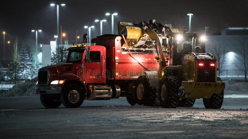 Snow Removal with Tandem Dumptruck and Loader. Edmonton, Alberta, Canada - 26.01.2018: Edmonton`s first big snowfall of the winter season had snow removal crews stock photos