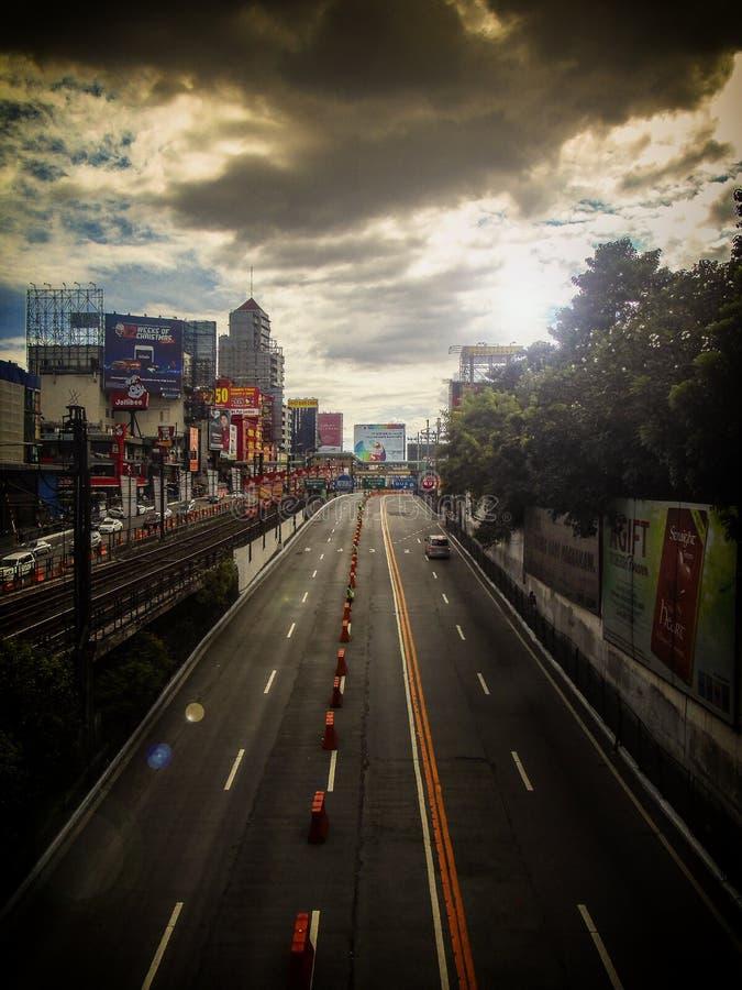 Edsa瓜达卢佩河在马卡蒂市,菲律宾-训练铁路、企业和美好的云彩形成 库存图片