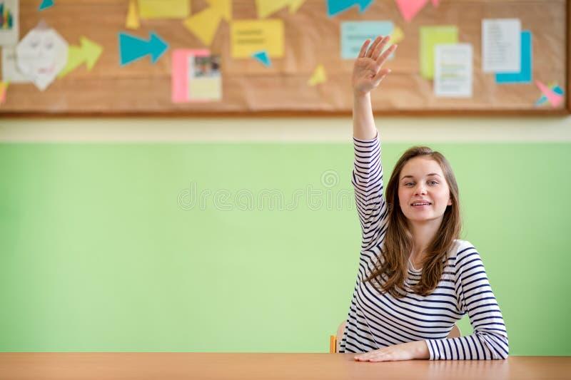 Educação, aprendizagem e conceito dos adolescentes Estudante que senta-se na sala de aula e que levanta a mão imagens de stock royalty free