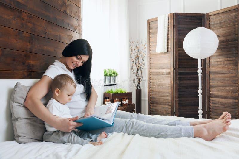 Educação da criança Mãe feliz com sua criança que senta-se na cama e que lê um livro imagem de stock