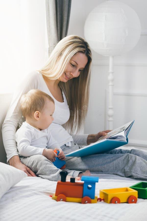 Educação da criança Mãe feliz com sua criança que senta-se na cama e que lê um livro foto de stock royalty free