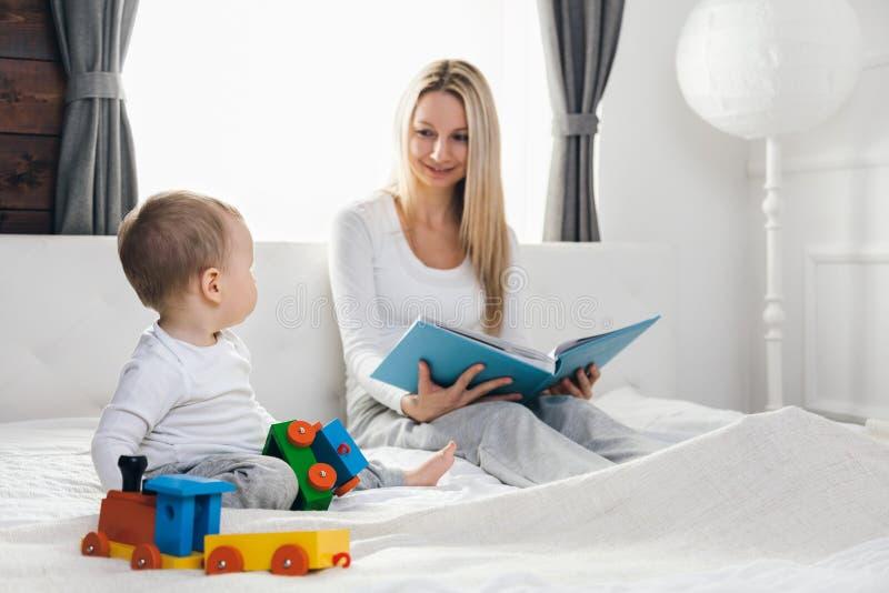 Educação da criança Mãe feliz com sua criança que senta-se na cama e que lê um livro fotografia de stock royalty free