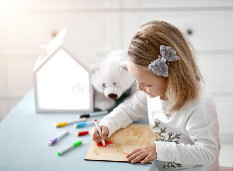 Educação de tiragem do jardim de infância feliz da menina da criança do bebê da criança com os marcadores coloridos na sala inter fotos de stock