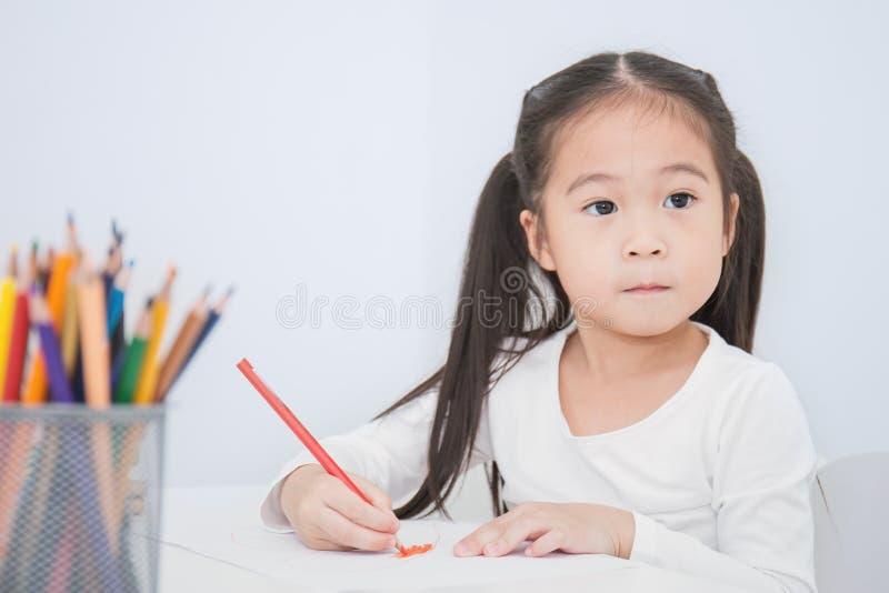 Educação e conceito da escola, desenho asiático pequeno da menina do estudante com os lápis na escola fotografia de stock royalty free