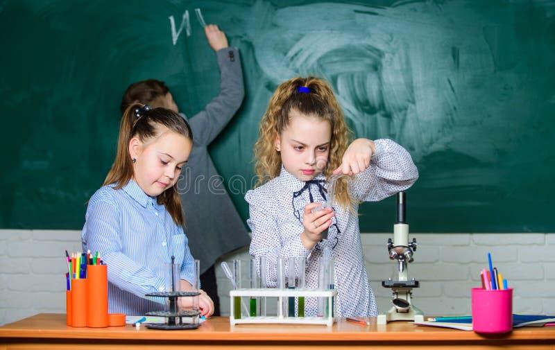 Educação escolar As meninas da escola estudam Crianças na sala de aula com microscópio e tubos de ensaio Explore moléculas biológ imagens de stock royalty free