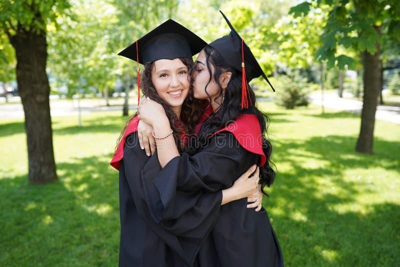 Educação, formatura e concepção das pessoas - encerramento de estudantes felizes raparigas ao ar livre foto de stock royalty free