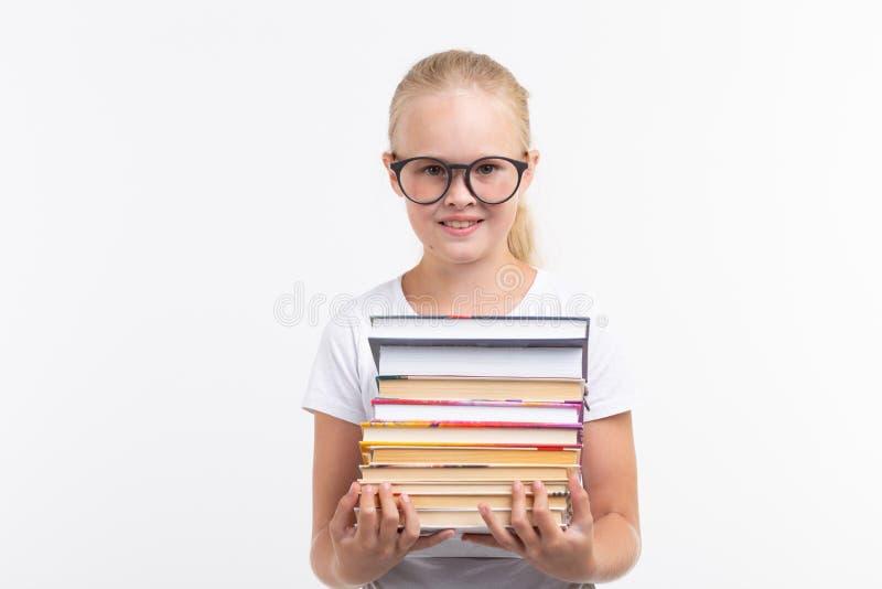 Educação, povos, crianças e conceito da escola - estudante da escola nos óculos de proteção que guardam livros nas mãos no fundo  fotografia de stock