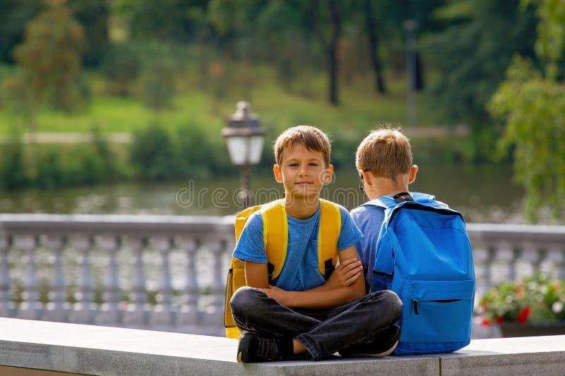 Educação primária, de volta à escola, à amizade, à infância, à comunicação e ao concep dos povos - crianças com assento da trouxa imagem de stock