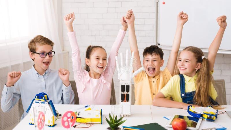 Educa??o da HASTE Crianças que levantam as mãos após ter feito robôs imagem de stock royalty free