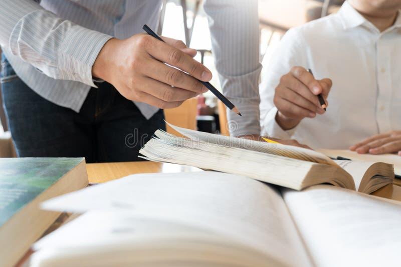 A educa??o e o conceito da escola, terreno dos estudantes ajudam a leitura do amigo da institui??o tutoria e o exame e a aprendiz imagens de stock