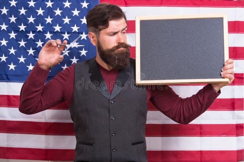 Educa??o patri?tica Homem farpado que guarda tesouras e quadro-negro na escola da educação Cursos do barbeiro hipster fotografia de stock royalty free