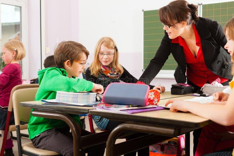 Educación - alumnos y profesor que aprenden en la escuela