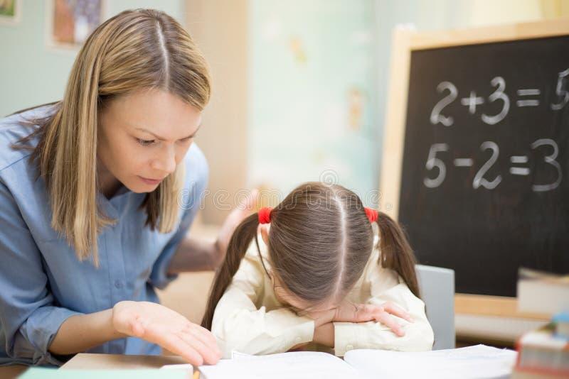 Educación casera preescolar La chica joven hermosa está enseñando en casa con la madre exigente fotos de archivo