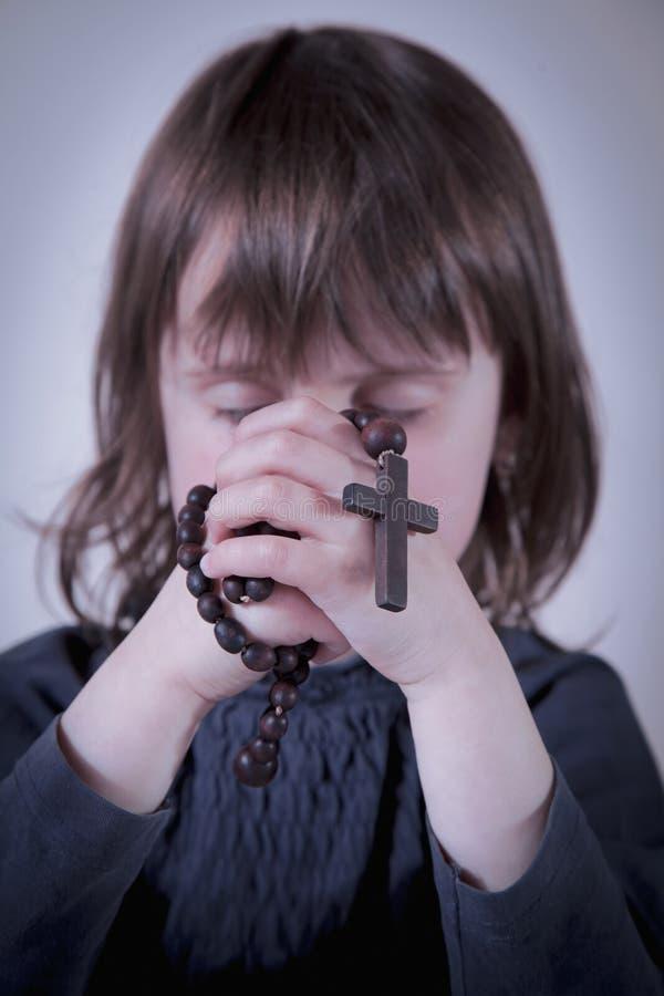 Educación de la educación religiosa del niño Poco muchacha linda que ruega y que sostiene un rosario imagen de archivo