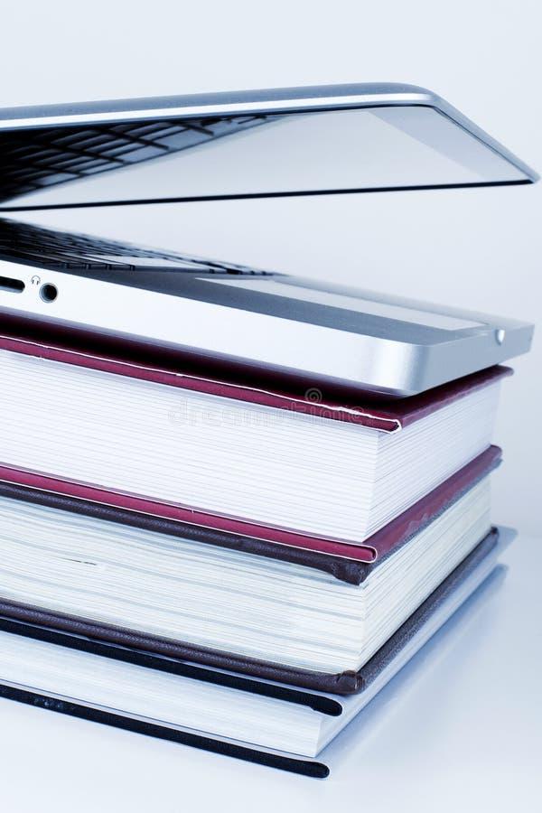 Educación en línea de la biblioteca que aprende concepto con el ordenador portátil y los libros fotos de archivo libres de regalías