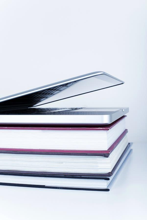 Educación en línea de la biblioteca que aprende concepto con el ordenador portátil y los libros fotografía de archivo