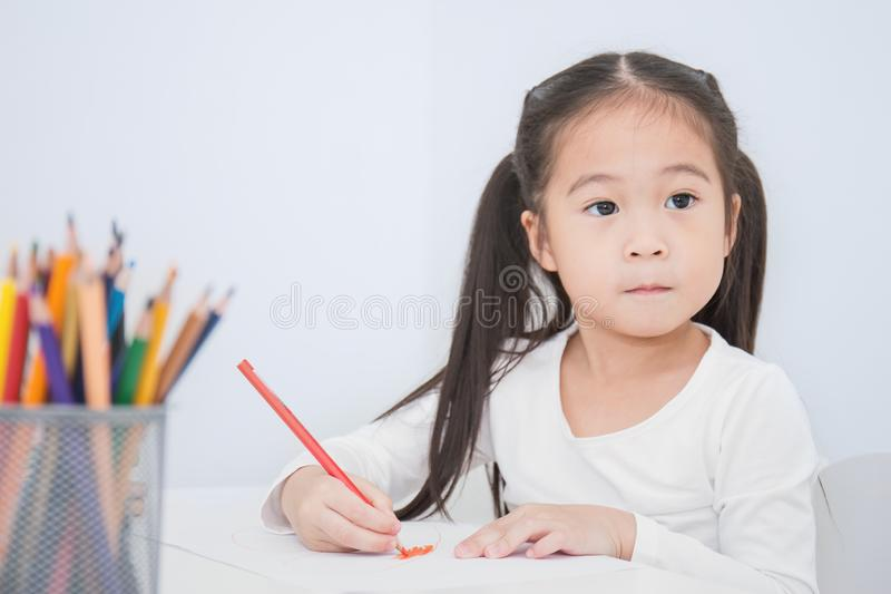 Educación y concepto de la escuela, pequeño dibujo asiático de la muchacha del estudiante con los lápices en la escuela fotografía de archivo libre de regalías