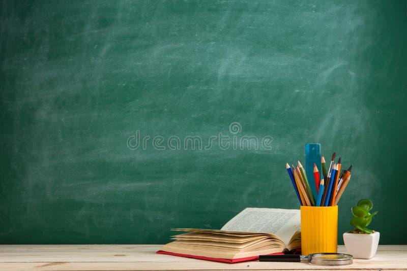 Educación y concepto de la lectura - grupo de libros coloridos en la tabla de madera en la sala de clase, fondo de la pizarra imagen de archivo libre de regalías