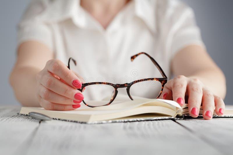 Educación y concepto del negocio - lentes que llevan de la empresaria en oficina imagen de archivo libre de regalías
