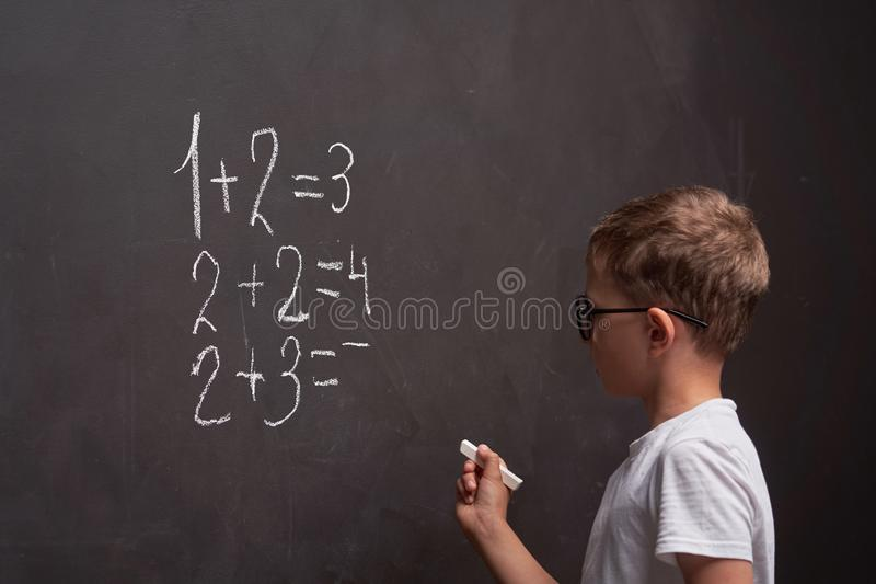Educaci?n primaria La vista posterior de un colegial soluciona un ejemplo matemático en una pizarra en una clase de la matemática foto de archivo