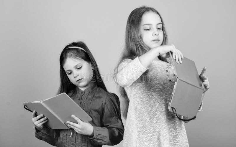 Educaci?n y literatura de los ni?os Cuento de hadas preferido Las hermanas escogen los libros para leer juntas Las muchachas ador imagen de archivo libre de regalías