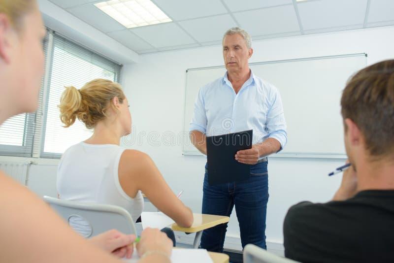 Educador mayor que habla con los adultos de los jóvenes de la clase fotos de archivo