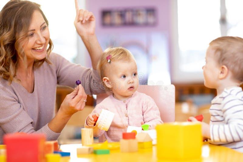 Educador y niños que se divierten en el aprendizaje en guardería Profesor, educación, niños y concepto de la escuela primaria foto de archivo