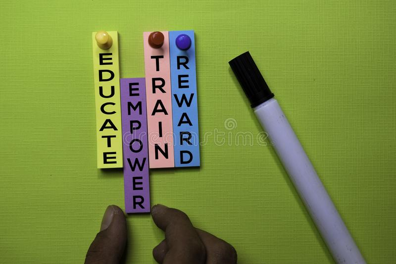 Educate, Train, Empower, Reward text on sticky notes isolated on green desk. Mechanism Strategy Concept royalty free stock photo