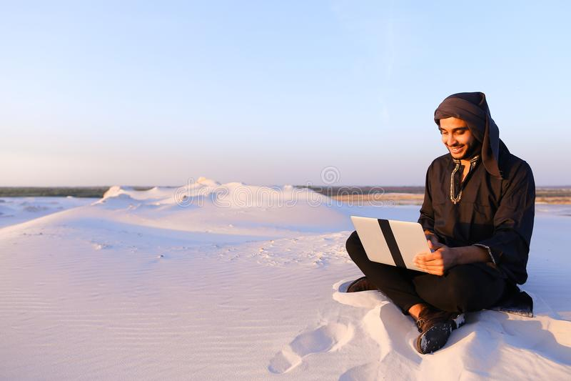 Educated Arab student uses laptop and works sitting on sand amid royalty free stock photos