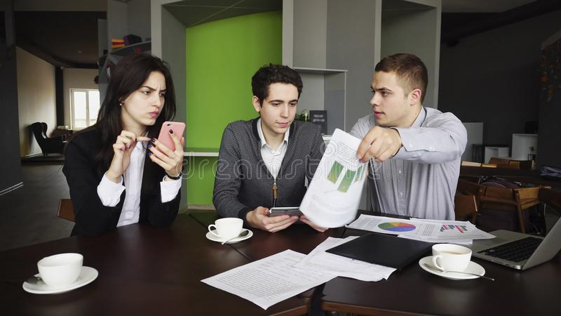 Serious managers, two men and women are burdened with work, use stock photo