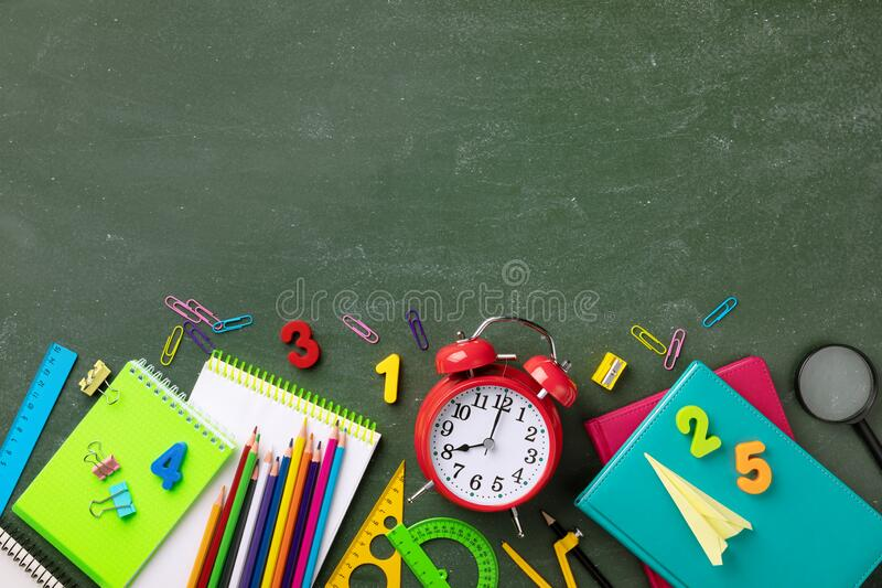 Education and back to school background with red alarm clock and stationery supplies on blackboard top view. Starting new school royalty free stock images