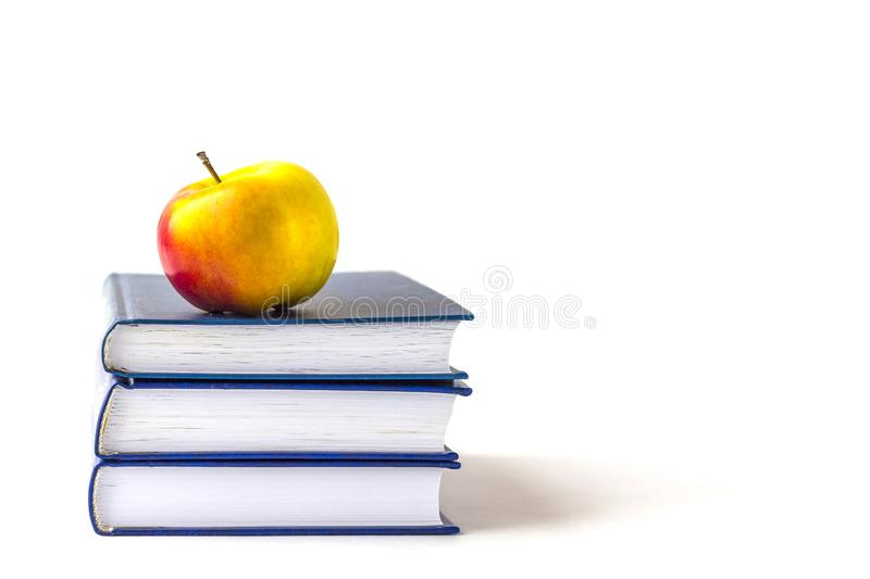 Education or back to school concept. An appleon a stack of books isolated on a white background with copy space royalty free stock images