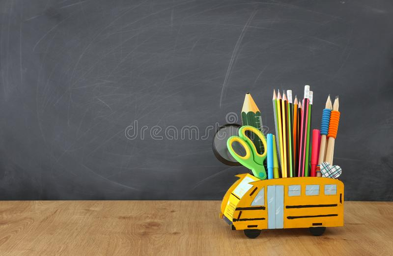 Education and back to school concept. pencils stand as bus over wooden desk infront of classroom blackboard stock photos