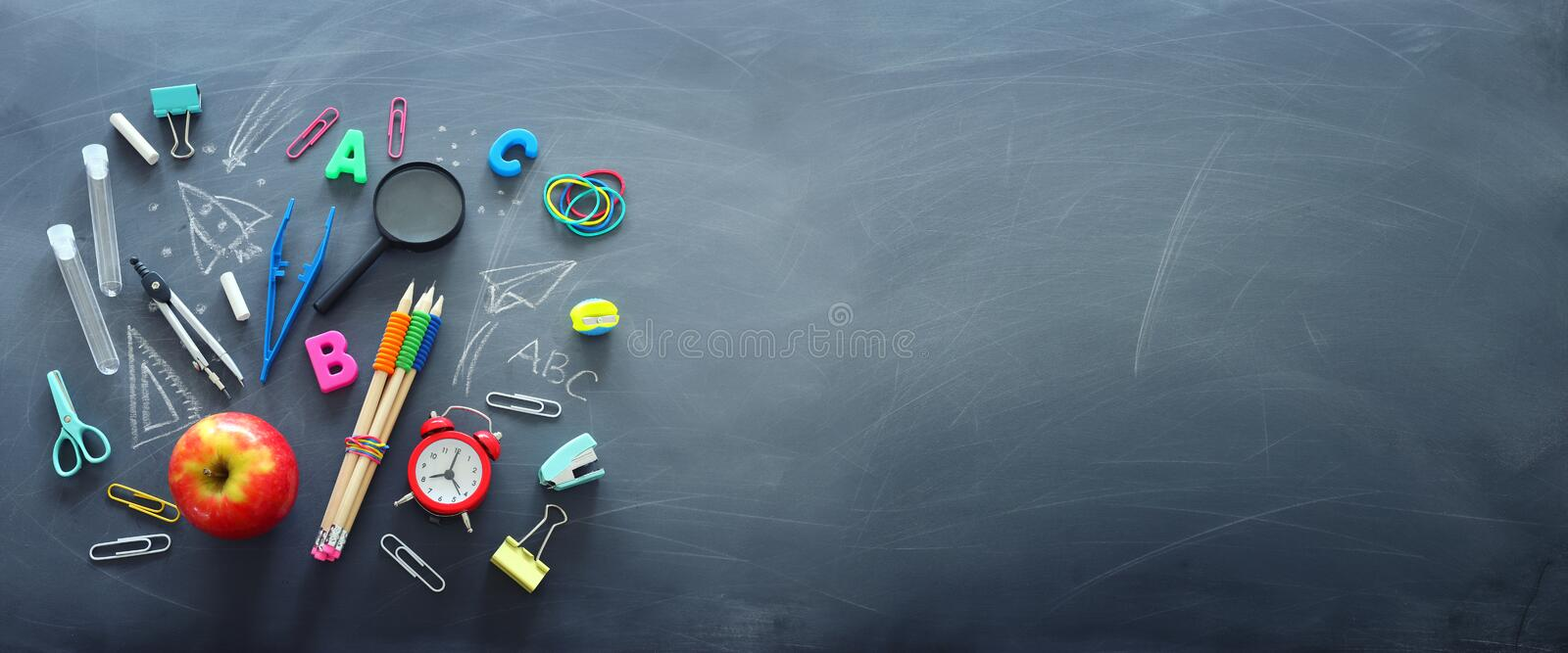 Education and back to school concept. shapes cut from paper and painted of backpack, books, chemistry flask and apple over royalty free stock photos