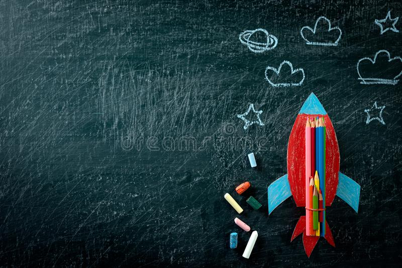 Education or back to school Concept. Top view of Painted paper rocket with colorful of color pencil and chalk on chalkboard. Background. Flat lay royalty free stock images