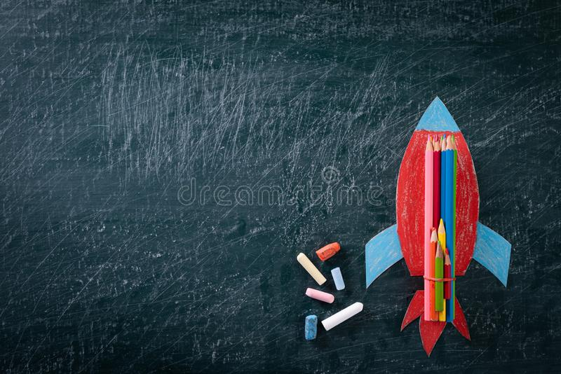 Education or back to school Concept. Top view of Painted paper rocket with colorful of color pencil and chalk on chalkboard. Background. Flat lay royalty free stock image