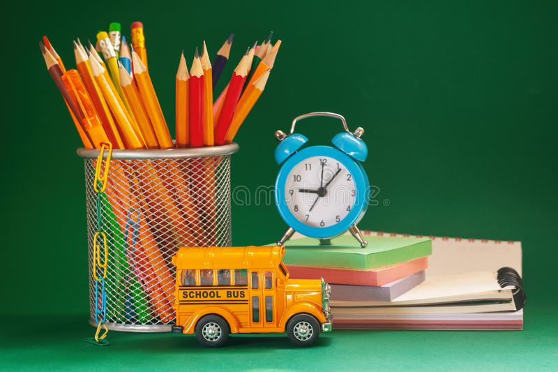 Education and back to school concept. Yellow retro school bus and pencils in basket, textbooks and alarm clock on dark green backg. Round royalty free stock photography