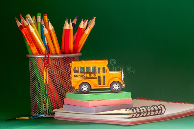 Education and back to school concept. Yellow retro school bus and pencils in basket, textbooks on dark green background. Education and back to school concept royalty free stock photos
