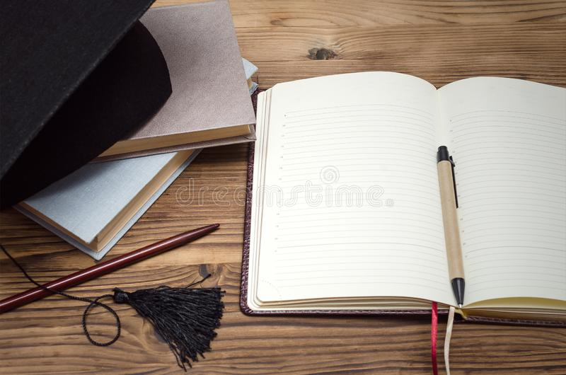 Education background. Graduate cap, stack of books and workbook with blank pages on the wooden school desk with copy space royalty free stock images