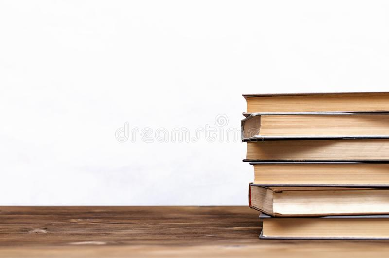 Education background. Graduate cap, stack of books and workbook with blank pages on the wooden school desk with copy space royalty free stock photo