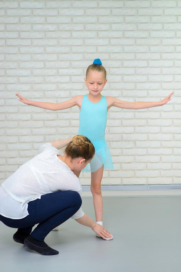 Education in ballet school. Teacher corrects pose of little ballerina in class. Cute little girl during dance practice. royalty free stock image